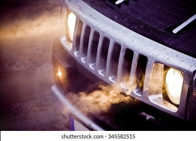 Car headlights and chrome grille of a big powerful American SUV Hummer H2. Fog in the headlights of a black expensive off road car. Bad fuel milage or economy