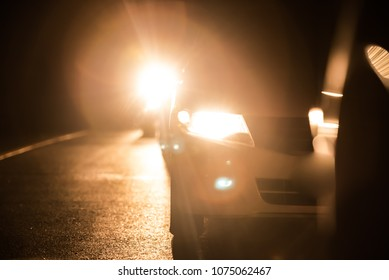 Car headlights high beam at night with bokhe on the street at night time, Abstract art blurred background in dark.