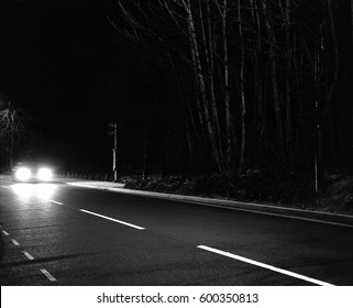 Car headlights at night on deserted country road