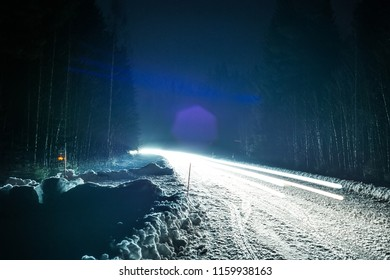 Car headlights on a winter road in the forest, on long exposure