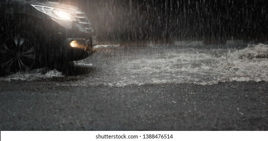 Car with headlights run through flood water after hard rain fall at night.