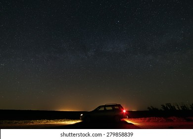 The car with the headlights switched on the background of the Milky Way in the starry sky.