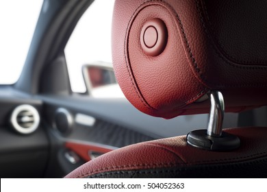 Car headrest seat in modern luxury comfortable car with red perforated leather