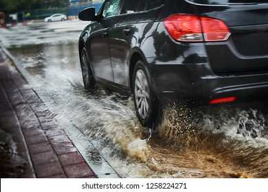 A car at high speed drives through a large puddle, Rain splash, raindrops and circles on the water. Israel, Rain, Flooding on the road