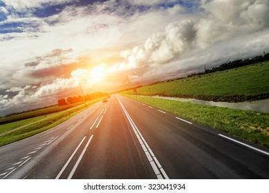 Car Highway at sunset and contrast cloudy sky.