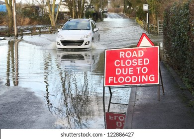 car ignoring road closed because of flooding sign