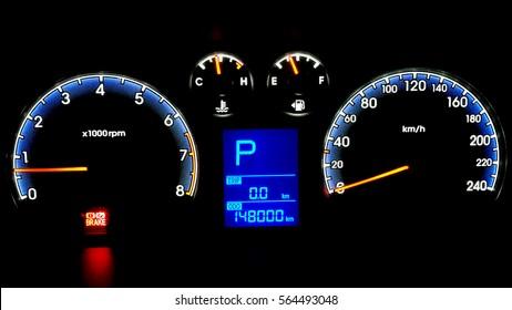 car illuminated dashboard closeup. tachometer on black background. Parking status.