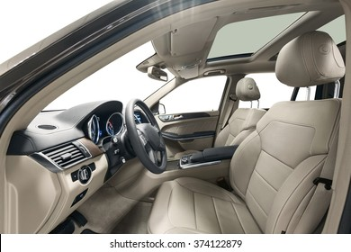 Car inside driver place. Interior of prestige modern car. Front seats with steering wheel & dashboard. Beige cockpit with wood decoration & panoramic roof on isolated white background.