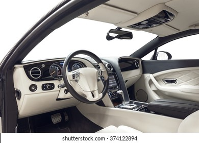 Car inside driver place. Interior of prestige modern car. Front seats with steering wheel & dashboard. Beige cockpit on isolated white background.