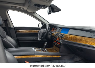 Car inside driver place. Interior of prestige modern car. Front seats with steering wheel, dashboard & gear shift. Black cockpit with wood decoration on isolated white background.