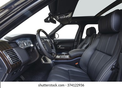 Car inside driver place. Interior of prestige modern car. Front seats with steering wheel, dashboard & climate control. Black cockpit with wood decoration on isolated white background.