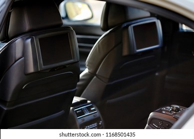 Car inside. Interior of prestige luxury modern car. Two displays for back seats passenger with media control panel copy space mock up.