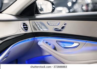 Car inside. Interior of prestige modern car. Climate control, hi-end sound speakers, seat memory, door lever & side mirror. White cockpit with wood & metal decoration & blue ambient light.