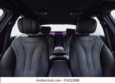 Car inside. Interior of prestige modern car. Comfortable leather seats. Black cockpit with violet ambient light on isolated white background.