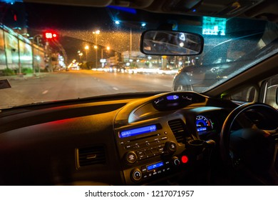 Car inside with night road view and street traffic light