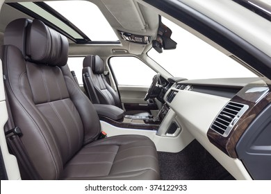 Car inside passenger place. Interior of prestige modern car. Front brown seats with steering wheel, dashboard. Beige cockpit with wood decoration on isolated white background.
