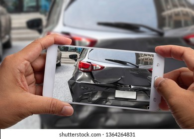 Car insurance agents take pictures of black car accident-damaged vehicles with a smartphone as a proof of insurance claim.