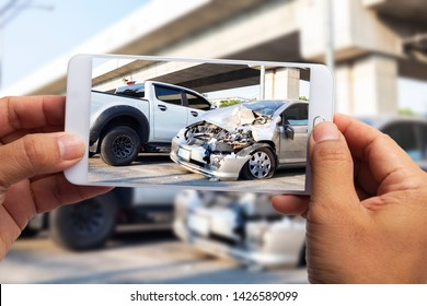 Car insurance agents take pictures of car accident-damaged vehicles with a smartphone as a proof of insurance claim.