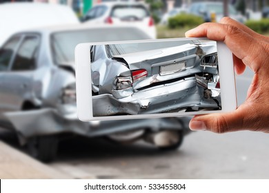 Car insurance agents take pictures of accident-damaged vehicles with a smartphone as a proof of insurance claim.