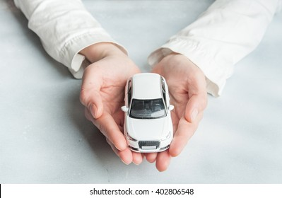 Car insurance. Automobile collision damage waiver concepts. with protective gesture and icon of car. Protection of car. Business concept. toy car and hand  isolated on white