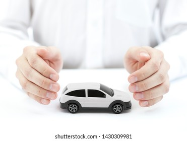 Car insurance concept with white car toy covered by hands