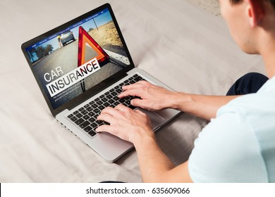 Car insurance in a laptop screen. Man looking for insurance company on the internet.