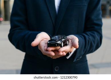 Car insurance. Car sale. Man in suit holding black car in hands with protective gest. Black toy car in the men's hand on a grey background.  Automobile collision damage waiver concepts.