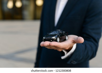 Car insurance. Car sale. Man in suit holding black car on the palm with protective gest. Black toy car in the men's hand on a grey background.  Automobile collision damage waiver concepts.