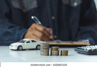 Car insurance and car service. Businessman with stack of coins and toy car, business and financial concept.