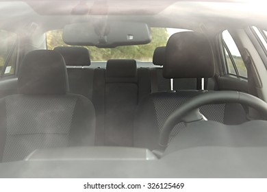 Car interior behind flaring reflections of the windscreen