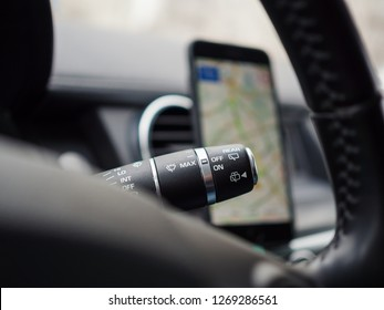 Car interior details: Stalk switch on a background of a smartphone with navigation map, selective focus