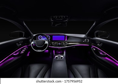 Car interior from driver seat view. Black leather cockpit with violet ambient light.