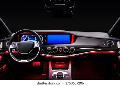 Car interior from driver seat view. Black leather cockpit with red ambient light.