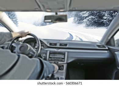 Car interior with drivers hands and winter road of snow and ice
