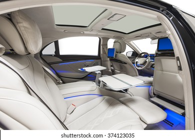 Car interior luxury. Back seats with tables & multimedia, climate control, display, wood decoration & blue ambient light