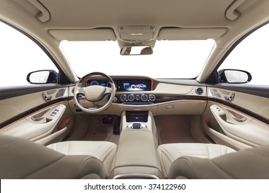 Car interior luxury. Beige comfortable seats, steering wheel, dashboard, climate control, speedometer, display, wood decoration & orange ambient light