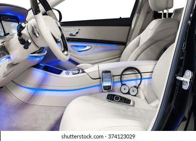 Car interior luxury. Beige leather, steering wheel, climate control, speedometer, display, wood decoration, phone, headphones & blue ambient light