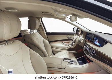 Car interior luxury. Interior of prestige modern car. Leather comfortable seats, dashboard & steering wheel. Beige cockpit with exclusive wood & metal decoration on isolated white background.
