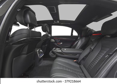 Car interior luxury. Interior of prestige modern car. Leather comfortable seats & panoramic roof. Black cockpit with exclusive wood & metal decoration on isolated white background. Red ambient light