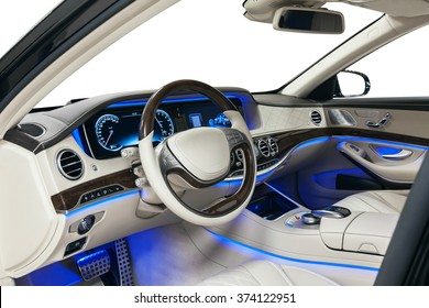 Car interior luxury steering wheel. Beige leather, dashboard, climate control, speedometer, display, wood decoration & blue ambient light