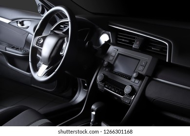 Car interior. Modern car speedometer, illuminated dashboard and steering wheel.