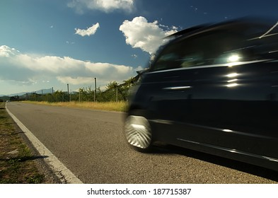 The car. An Italian car runs fast on a country road.