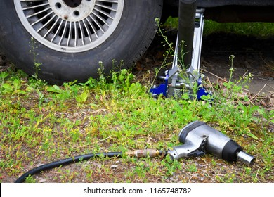 Car jack and impact torque wrench near a car tire