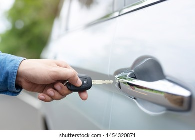 Car key in business man hand.  hand presses on the remote control car alarm systems. lock or unlock the door.