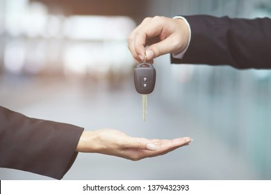 Car key, businessman handing over gives the car key to the other woman on showroom background.