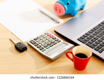 Car key and calculator with office supplies on wood table desk