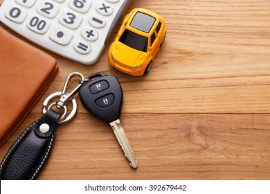 Car key with calculator and pocket money on wood table background