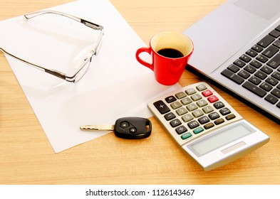 Car key and calculator with red coffee cup and paper notepad on wood table desk