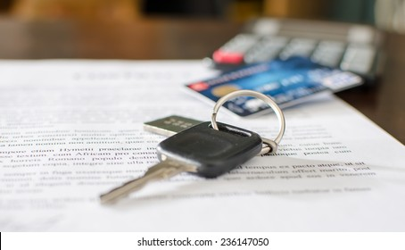 Car key, credit card on a signed sales contract, closeup