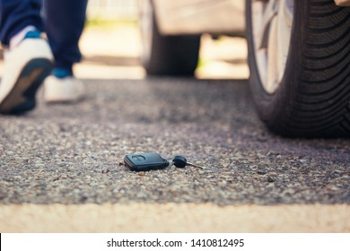 Car key fall on the asphalt road. Driver lost his vehicle keys and walks away. Misfortune concept.
